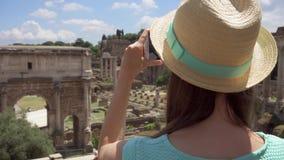 Mujer cerca del foro Romanum que toma la foto en el teléfono móvil Turista femenino que toma la imagen del foro romano almacen de video