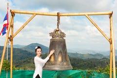 Mujer cerca del gongo tailandés en Phuket Campana asiática de la tradición en templo del budismo en Tailandia Deseo grande famoso Imagenes de archivo
