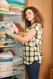 Mujer cerca del guardarropa con ropa de cama Foto de archivo