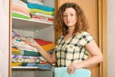 Mujer cerca del guardarropa con ropa de cama Imágenes de archivo libres de regalías