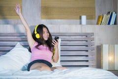 Mujer china asiática atractiva y feliz joven con los auriculares amarillos que escucha la música en teléfono móvil en la cama en  imagen de archivo