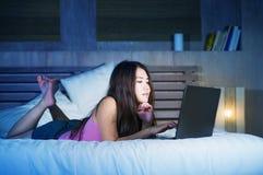 Mujer china asiática atractiva y hermosa joven 20s que miente en cama en la noche usando Internet en el ordenador portátil que mi Imagenes de archivo
