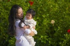 Mujer china asiática feliz y linda joven que goza y que juega con su hija del bebé que celebra y que besa su sonrisa alegre imagen de archivo libre de regalías