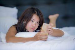 Mujer china asiática hermosa joven con el auricular que escucha la mentira feliz sonriente de la música en cama usando Internet e Foto de archivo libre de regalías