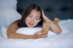 Mujer china asiática hermosa joven con el auricular que escucha la mentira feliz sonriente de la música en cama usando Internet e Fotografía de archivo libre de regalías
