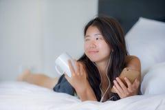 Mujer china asiática hermosa joven con el auricular que escucha la mentira feliz sonriente de la música en cama usando Internet e Fotos de archivo libres de regalías