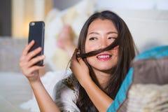 Mujer china asiática hermosa y feliz joven que miente en casa sofá del sofá usando Internet que fecha el app en el teléfono móvil fotos de archivo libres de regalías