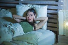 Mujer china asiática hermosa y subrayada joven que tiene insomnio que miente en la tensión de la ansiedad de la cama y la cabeza  imagen de archivo libre de regalías