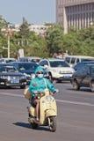 Mujer china con el casquillo de la boca en la e-bici, Pekín, China Imagenes de archivo