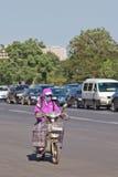 Mujer china con el casquillo de la boca en la e-bici, Pekín, China Fotos de archivo libres de regalías