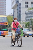Mujer china con el casquillo en una bicicleta, Kunming, China de la boca Imágenes de archivo libres de regalías