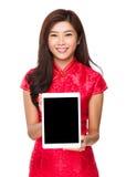 Mujer china con la demostración del cheongsam con la tableta Fotos de archivo
