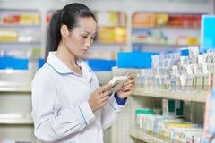 Mujer china del químico de la farmacia en droguería de China fotos de archivo
