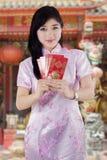 Mujer china en el vestido del cheongsam que da el sobre Foto de archivo