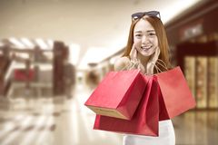 Mujer china feliz con las bolsas de papel rojas en la alameda foto de archivo