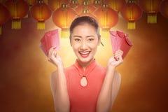 Mujer china hermosa en un vestido tradicional que lleva a cabo el envel rojo Imagenes de archivo