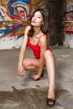 Mujer china hermosa que se pone en cuclillas abajo por las paredes de la pintada Fotos de archivo
