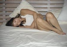 Mujer china hermosa y bastante asiática joven que miente en la cama que siente calambre sufridor enfermo y mal del vientre y de e foto de archivo