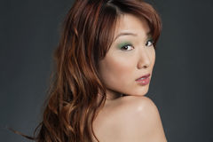 Mujer china joven hermosa que mira detrás sobre fondo coloreado Fotografía de archivo