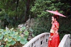 Mujer china joven, hermosa y elegante que lleva el vestido rojo de seda de una novia china típica, adornado con Phoenix y drago d imagenes de archivo