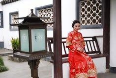 Mujer china joven, hermosa y elegante que lleva el vestido rojo de seda de una novia china típica, sentada adornada en banco del  fotografía de archivo libre de regalías