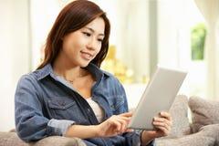 Mujer china joven que usa la tablilla de Digitaces Imagen de archivo libre de regalías