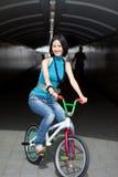 Mujer china peculiar, cobarde en la bici de la calle Foto de archivo
