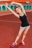 Mujer china que estira en pista en el estadio Imagenes de archivo