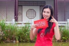Mujer china que sostiene el paquete rojo feliz durante la estación china del Año Nuevo Imagen de archivo libre de regalías