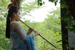 Mujer china que toca la flauta de bambú Fotos de archivo