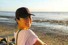 Mujer china sana joven que mira la puesta del sol en la playa foto de archivo