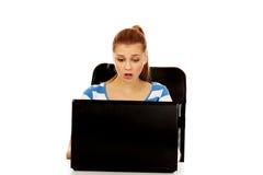 Mujer chocada adolescente con el ordenador portátil que se sienta detrás del escritorio Imagen de archivo libre de regalías