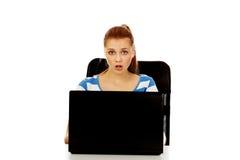 Mujer chocada adolescente con el ordenador portátil que se sienta detrás del escritorio Imágenes de archivo libres de regalías