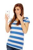 Mujer chocada adolescente que lee un mensaje en el teléfono móvil Imagenes de archivo