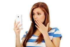 Mujer chocada adolescente que lee un mensaje en el teléfono móvil Fotografía de archivo libre de regalías