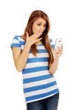 Mujer chocada adolescente que lee un mensaje en el teléfono móvil Fotos de archivo libres de regalías
