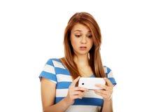 Mujer chocada adolescente que lee un mensaje en el teléfono móvil Fotografía de archivo