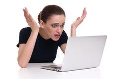 Mujer chocada con el ordenador portátil foto de archivo