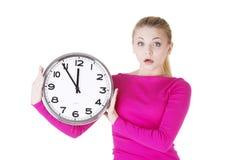 Mujer chocada con el reloj Fotos de archivo