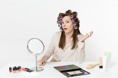 Mujer chocada con los bigudíes en el pelo que se sienta en la tabla que aplica maquillaje con los cosméticos decorativos faciales fotos de archivo