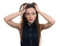 Mujer chocada con sus manos en la cabeza fotografía de archivo