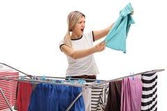 Mujer chocada detrás de un secador del estante de la ropa que mira una camisa fotografía de archivo