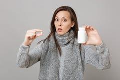 Mujer chocada en el suéter gris, tabletas de la medicación del control de la bufanda, píldoras de aspirin en la botella aislada e imagen de archivo