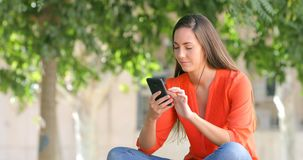 Mujer chocada en el teléfono en un parque almacen de metraje de vídeo