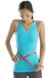Mujer chocada en la ropa de los deportes que mide su cintura Imagenes de archivo