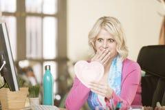 Mujer chocada en su oficina con Valentine Heart Fotos de archivo libres de regalías