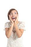 Mujer chocada feliz que mira el lado con las manos en cara Imagen de archivo