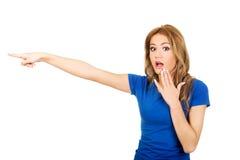Mujer chocada hermosa que señala a un lado Imagen de archivo libre de regalías