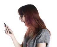 Mujer chocada que hace frente en el teléfono móvil en su mano Imagenes de archivo