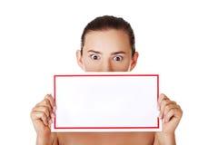 Mujer chocada que lleva a cabo al tablero en blanco Imagenes de archivo